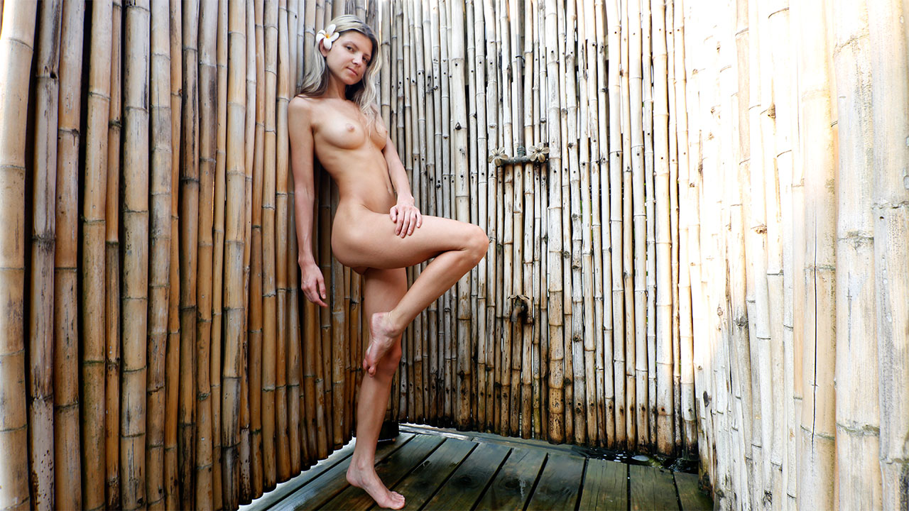 Gina Gerson poses in outdoor villa shower