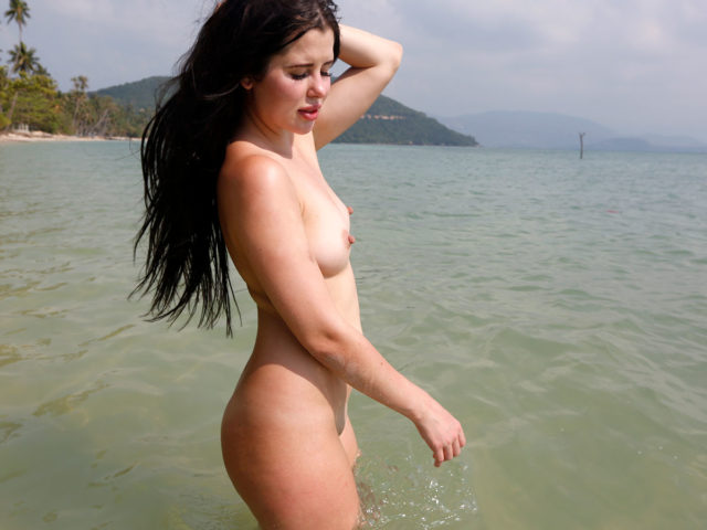 Nude Beach Slut rinses her pussy out in the sea